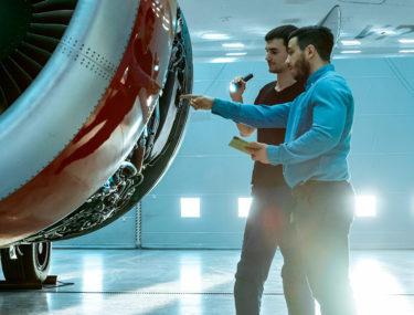 Two men checking aeroplane