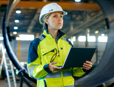 Woman in hard hat and holding laptop