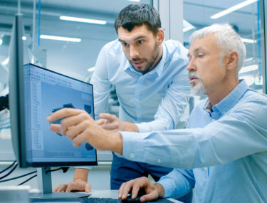 Two men discussing designs on computer